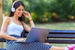 Young pretty woman sitting on bench in the park, using laptop computer Stock Photo