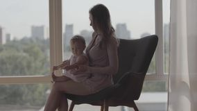 Young pretty woman sitting in the comfortable chair in front of the window holding baby girl in her arms. Concept of a. Young pretty woman sitting in the stock footage