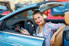 Young pretty woman sitting in a convertible car with the keys in Stock Photo