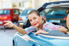 Young pretty woman sitting in a convertible car with the keys in Royalty Free Stock Photo