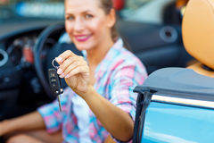 Young pretty woman sitting in a convertible car with the keys in Royalty Free Stock Images