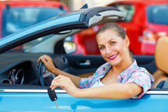 Young pretty woman sitting in a convertible car with the keys in Stock Photos