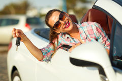 Young pretty woman sitting in a convertible car with the keys. In hand - concept of buying a used car or a rental car Royalty Free Stock Images