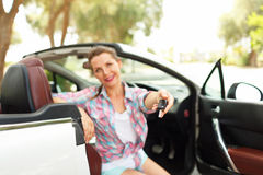 Young pretty woman sitting in a convertible car with the keys. In hand - concept of buying a used car or a rental car Royalty Free Stock Photo