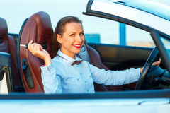Young pretty woman sitting in a convertible car with the keys. In hand - concept of buying a used car or a rental car Royalty Free Stock Photos