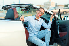 Young pretty woman sitting in a convertible car with the keys in. Hand - concept of buying a used car or a rental car Royalty Free Stock Photography