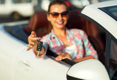 Young pretty woman sitting in a convertible car with the keys in. Hand - concept of buying a used car or a rental car Royalty Free Stock Photos