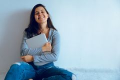 Young pretty woman sitting on the floor with laptop Stock Photo