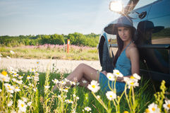 Young pretty woman sitting near green car Royalty Free Stock Photography