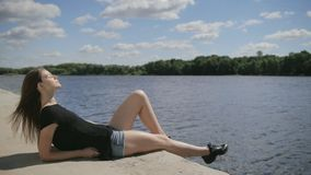 Young pretty woman sitting near river with closed eyes stock footage