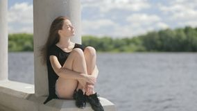Young pretty woman sitting near river with closed eyes stock video