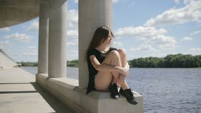 Young pretty woman sitting near river looking aside stock video