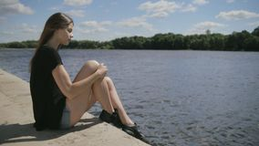 Young pretty woman sitting near river looking at river stock video