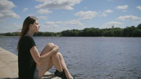 Young pretty woman sitting near river looking at river stock footage