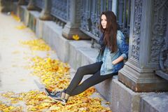 Young pretty woman sitting pensively on a stone slab a beautiful iron fence with his hands in the pockets of a denim. Jacket around the yellow autumn leaves of Stock Image