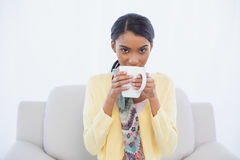 Young pretty woman sitting on sofa drinking coffee Royalty Free Stock Photos