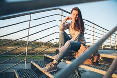 Young pretty woman sitting on the stairs of the mall Stock Photo