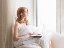 Young pretty woman sitting on window with laptop and working stock photos