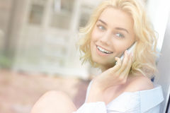 Young pretty woman sitting in the window and talking on phone Royalty Free Stock Photos