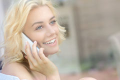Young pretty woman sitting in the window and talking on phone Stock Images