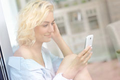 Young pretty woman sitting in the window and texting Stock Photo