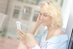 Young pretty woman sitting in the window and texting Royalty Free Stock Images
