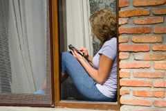 A young pretty woman is sitting on the windowsill and holding a. Phone in her hand. View from the street stock image