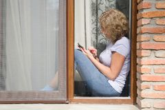 A young pretty woman is sitting on the windowsill and holding a. Phone in her hand. View from the street royalty free stock photos