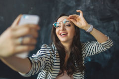 Young pretty woman with smartphone in her hand taking picture. Of herself in glasses Stock Photo