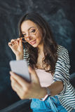 Young pretty woman with smartphone in her hand taking picture. Of herself in glasses Royalty Free Stock Photo