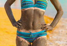 Young pretty woman smeared with mud on the beach Royalty Free Stock Image