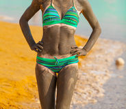 Young pretty woman smeared with mud on the beach Stock Photo