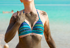 Young pretty woman smeared with mud on the beach Royalty Free Stock Photography
