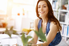 Young pretty woman smiling at her desk in office Stock Photography