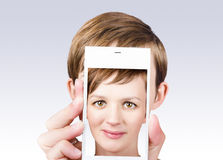 Young pretty woman smiling on smartphone screen Stock Photos