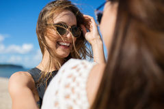 Young pretty woman smiling to her female friend royalty free stock photo