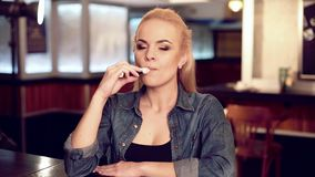 Young pretty woman in smoke an electronic cigarette at the vape shop. stock footage