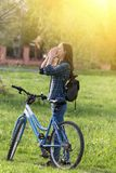 Woman having symptoms of spring pollen allergy. Young pretty woman sneezing while riding bicycle on grassland with spring flowers. Pollen allergy symptoms Stock Photography