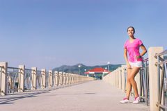 Young pretty woman. Sport lifestyle. Exercising outdoor. Young pretty woman resting after jogging drinking water on the sea pier Royalty Free Stock Images