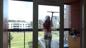 Young pretty woman spray chemical and wipe window at clients home. stock video