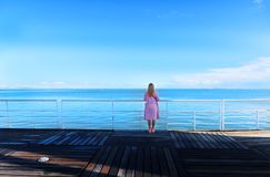 Young pretty woman standing alone on the pier near the sea royalty free stock photography