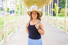 Young pretty woman is standing in the beautiful white colonnade in Karlovy Vary resort in Czech republic Stock Image