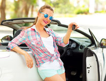 Young pretty woman is standing near the convertible car with the Stock Photos