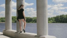 Young pretty woman standing near river stock video