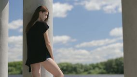 Young pretty woman standing near river stock video footage