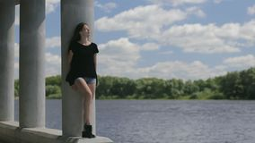 Young pretty woman standing near river stock footage
