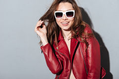Young pretty woman standing over grey wall wearing sunglasses. Stock Images