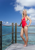Young pretty woman stands in bathing suit on platform at villa on water Stock Photo