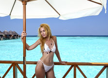 Young pretty woman stands in bathing suit on platform at villa on water, Maldives Royalty Free Stock Image
