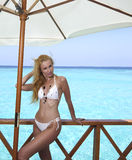 Young pretty woman stands in bathing suit on platform at villa on water, Maldives Royalty Free Stock Images